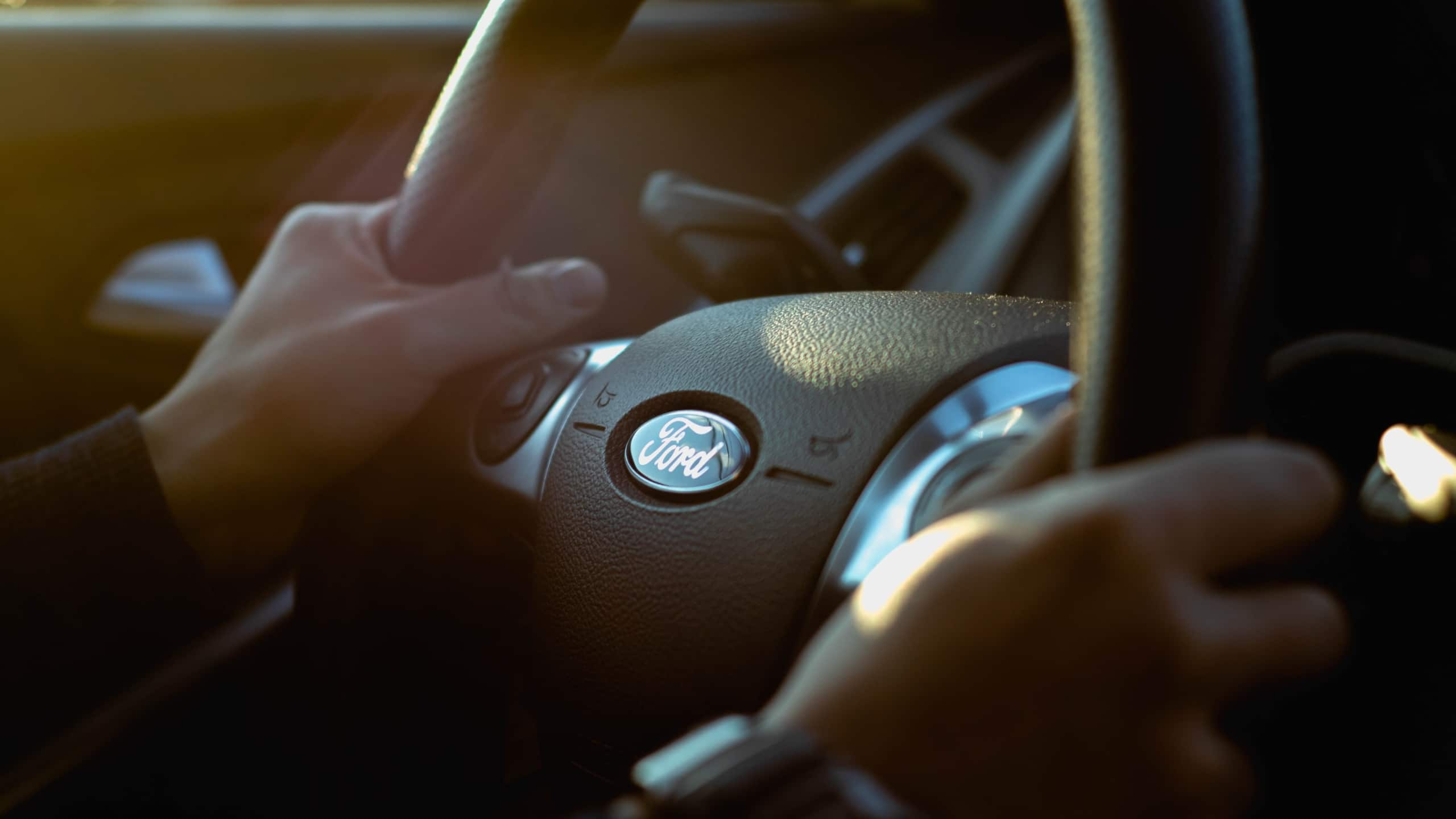 Person holding onto the steering wheel of a ford motor vehnicle